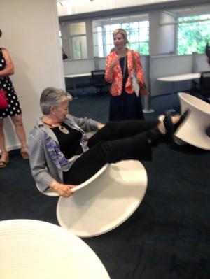 N.C. Commerce Secretary Sharon Decker has a little fun on a swirling novelty chair inside tekMountain. Photo by Ben Brown.