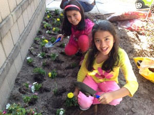 Kids in the Brigade's gardening program help plant flowers in the club's beautification project on Earth Day. Photo by Christina Haley.
