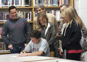 Michael Fasano signs letter of intent as his family watches on.