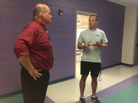 Ashley High School's new principal, Patrick McCarty, talks with a teacher Tuesday. McCarty plans to improve relations with staff, parents and students by spending more time in the hallways than his office. Photos by Hilary Snow.