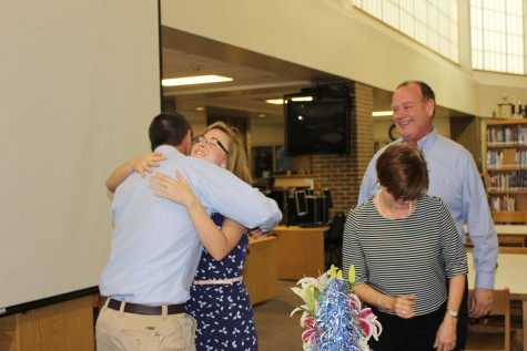 Katie Snyder hugs her family in Hoggard High School's media center Tuesday after a surprise announcement that she is the Southeast Region Teacher of the Year. Photos by Hilary Snow.