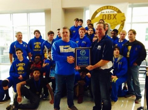 Coach Dan Willis accepts first-place trophy at this years OBX Tournament. Photo courtesy- Laney wrestling.