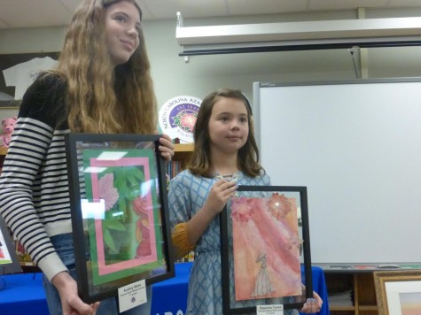 Middle school winner Audrey Mase, left, Torres pose with their first-place artwork.