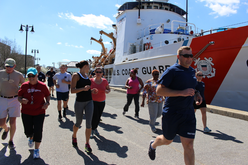 Crew members of the U.S. Coast Guard Cutter Diligence and community members begin their workout Tuesday with a run along downtown Wilmington's riverwalk. Photo by Christina Haley.