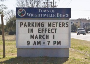 A sign reminded visitors and residents when parking season begins in Wrightsville Beach. Photo by Hannah Leyva.