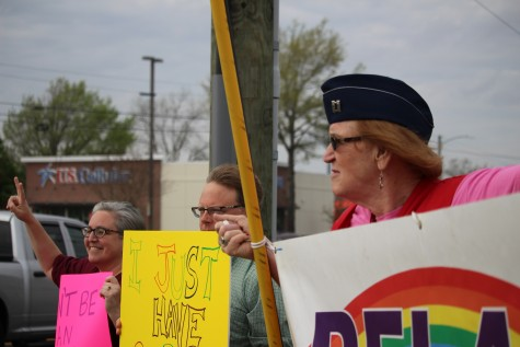 Rachael Gietchen, right, who transitioned in 2007 from a man to a woman, stands will fellow protesters along the intersection of College Road and Oleander Drive Friday. Photos by Hilary Snow.