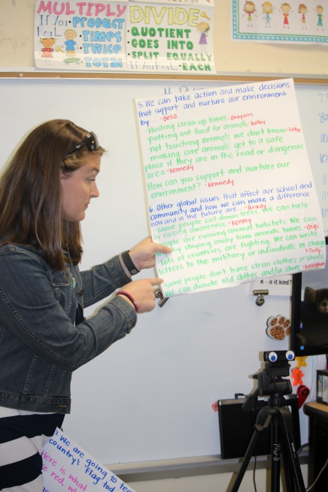 Teacher Margaret McLaurin holds cue cards to prompt students and keep them focused. Students came up with their own questions and did their own research in preparation for the Skype event.