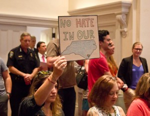 One of the many signs brought into Wilmington City Council Chambers on Tuesday night. Photo by Hannah Leyva.