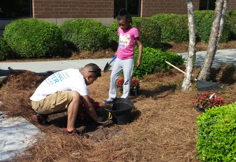 Luis Vargas, sales manager for U.S. Cellular in Wilmington, works with Brigade Boys and Girls Club member Hannah White to plant flowers and shrubs outside the Vance Street club as part of the company's second-annual 'Month of Giving' program. Courtesy photo.