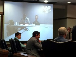 Eduard Patrick (right) on camera with a deputy for his first appearance in district court. Photo by Christina Haley.
