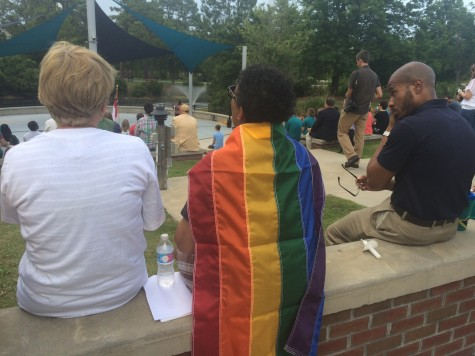 A gay pride flag draped over her, Shelia Melton listens, emotionally, to a spiritual at the conclusion of UNCW's vigil for the 49 killed and 53 injured in Sunday's attack on an Orlando nightclub. Photos by Hilary Snow.