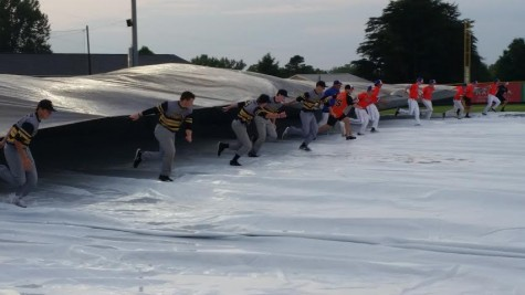 Both teams assisted in removing the tarp after a two-hour delay.
