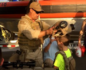 A U.S. Coast Guard member outfits a boy with military gear during National Night Out. Photos by Christina Haley.
