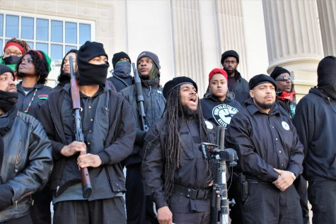 Alli Muhammad speaking at a news conference at the New Hanover County Courthouse. Many of the members carried weapons on their shoulders or holstered.