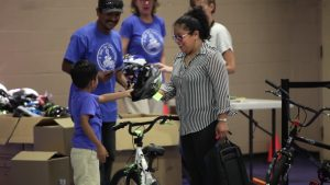 A child receives his new bike and helmet at last year's event. (Photo courtesy of A Bike for Every Child)