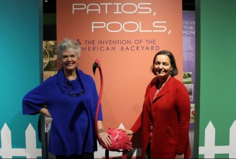 Kitty Yerkes, donor relations director, and Sheryl Mays, museum director, with a pink metal flamingo, on loan from the Stone Garden lawn and garden store in Wilmington, NC. (Photo Benjamin Schachtman)