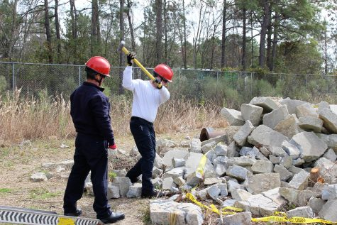 A firefighter works to break up concrete, as part of his search and rescue training.