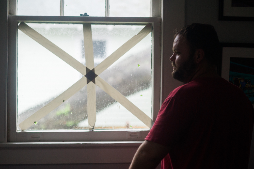 Stacy Ambrose stares out a window of a home in the Carolina Place neighborhood east of downtown Wilmington during the calm between the inner bands of Hurricane Florence Friday morning. Ambrose had earlier evacuated his home in Wrightsville Beach. (Port City Daily photo   Mark Darrough)