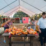 The Finch family, right, loads up a wagon of pumpkins for the season. (Port City Daily photo/Mark Darrough)