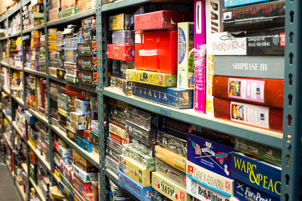 A row of shelves that currently house Darryl Rubin's collection of old and rare games inside the warehouse space behind Cape Fear Games. (Port City Daily photo/Mark Darrough)