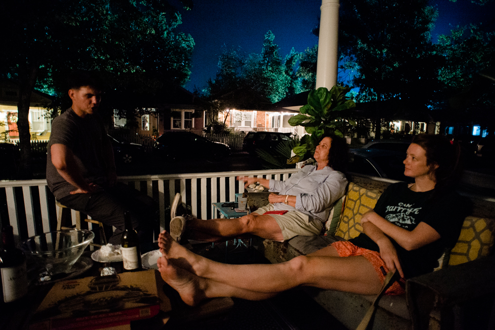 Neighbors talk on a front porch on Wrightsville Avenue as the lights of the film set shine behind them. (Port City Daily photo/Mark Darrough)