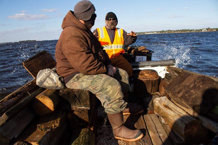 Joe Huie Jr. and Joshua Whitney sit amongst hundreds of pounds of marine debris collected from hard-to-reach areas of Carolina Beach State Park's shoreline. (Port City Daily photo/Johanna F. Still)
