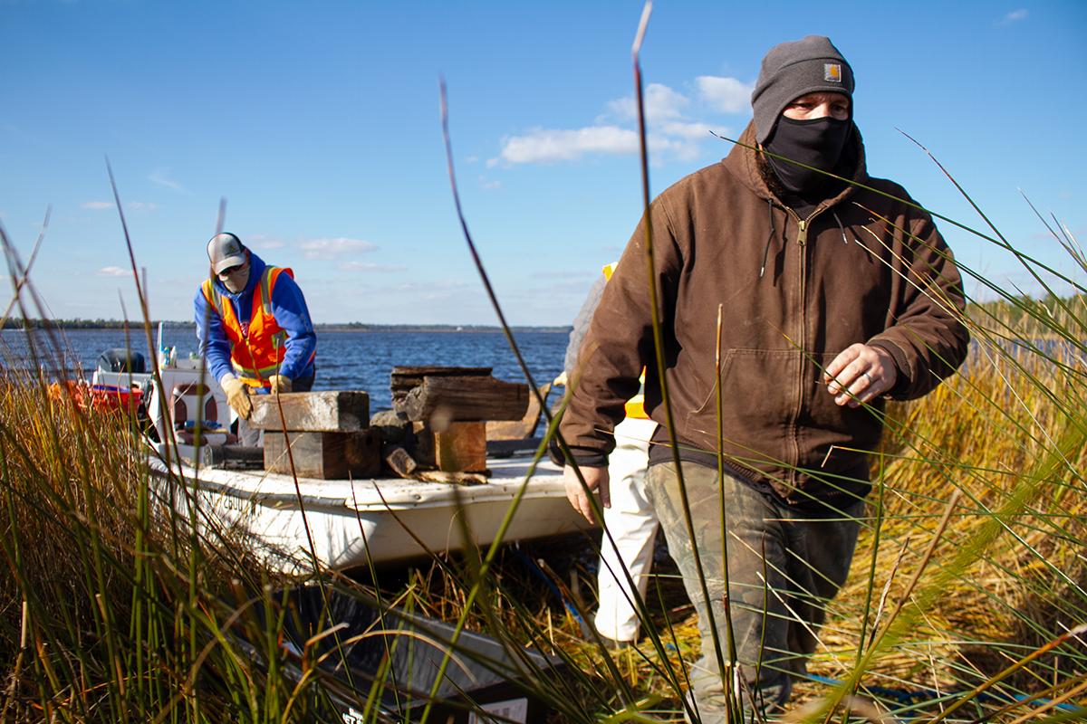 Crew supervisor Joe Huie Jr. makes his way through the marsh to access a deposit of marine debris inaccessible from the Carolina Beach State Park shoreline. (Port City Daily photo/Johanna F. Still)