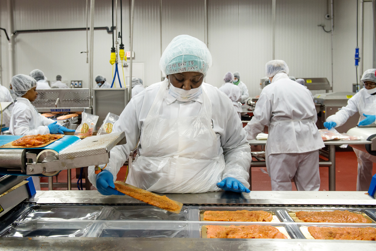 An Acme Smoked Fish production associate loads trays of sliced, cold-smoked salmon into packaging before it gets vacuum sealed and delivered to grocery stores across the nation. (Port City Daily photo/Courtesy Acme Smoked Fish)
