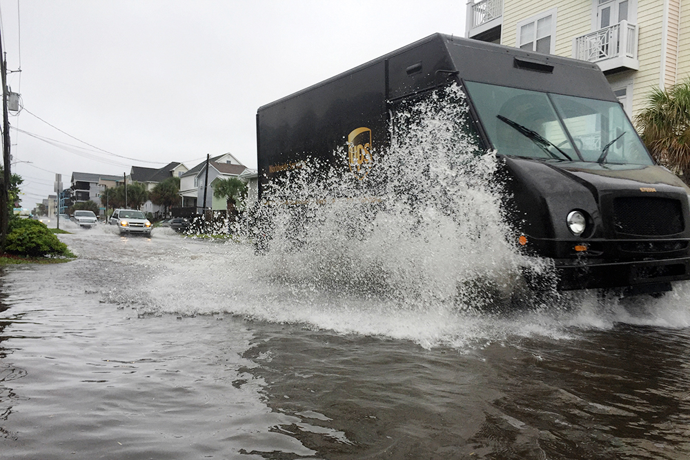 A UPS delivery truck drives through saltwater on Canal Drive in Carolina Beach. (Port City Daily photo/Johanna F. Still)